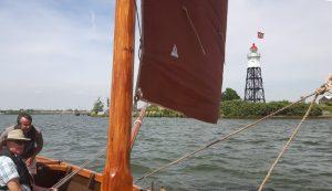 Foto vanaf de melkschuit naar de vuurtoren van Durgerdam met de vlag van Amsterdam in top